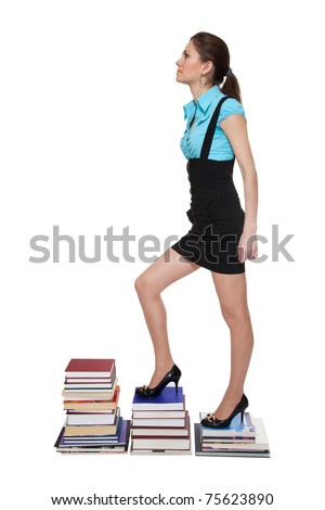 Young woman climb on stairs of books isolated on white