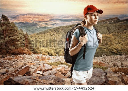 Young woman climber wearing cap with backpack hiking in mountain and hills Satisfied female traveler in sportswear trekking on sunset
