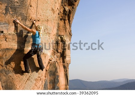 Young woman climbing a rock of sandstone