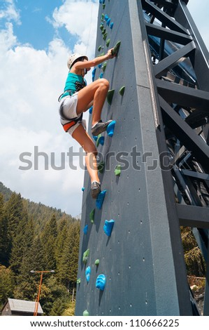 Young woman climbing and stretching and nearly at the summit