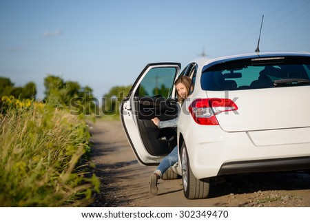 Young woman climbing into the rear passenger seat of a car stopped on a country road looking back to smile at the camera