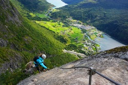 Young woman climbing on via ferrata Loen in Norway on a sunny day of summer