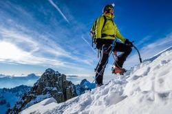 Young woman climbing snow ridge