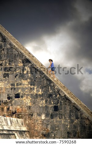 Young woman climbing the Pyramid at Chichen Itza - stock photo