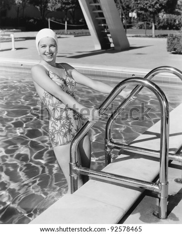 Young woman climbing up the ladder of a swimming pool