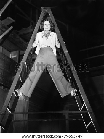 Young woman climbs a ladder to the top