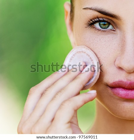 young woman closeup applying foundation