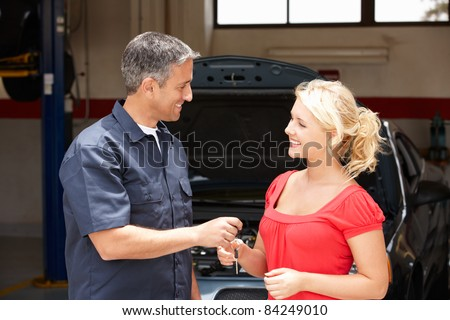 Young woman collecting care from repair shop