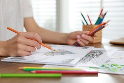 Young woman coloring antistress page at table indoors, closeup