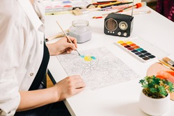 Young woman coloring page antistress at table indoors, mental wellbeing and art therapy. Woman paints a sketch, meditative process of coloring pages.