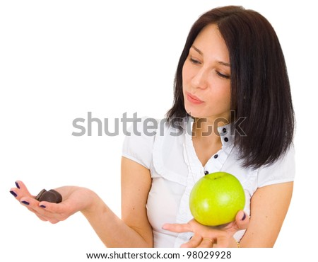 Young woman comparing apple with chocolates over white background