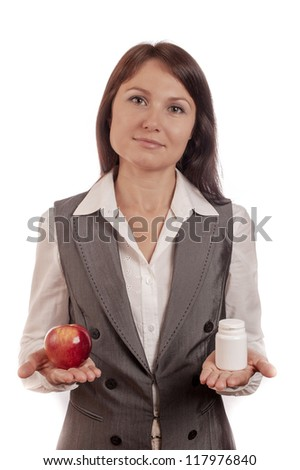 Young woman comparing apple with medicine over white background