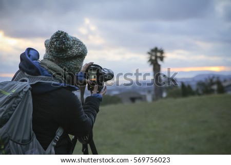 Young woman composes a photo at sunset in the east bay area looking west