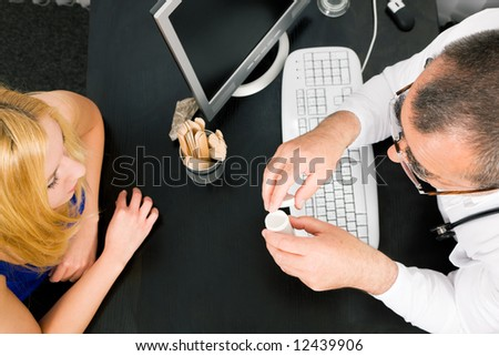 Young woman consulting her doctor, he has a prescription drug bottle in his hand