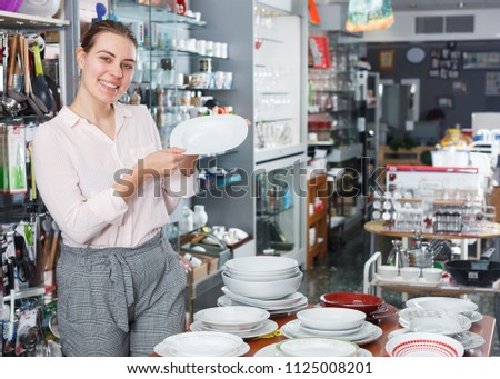 Young woman consumer ceramic plates  in the tableware shop #1125008201