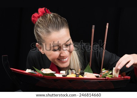Young woman cook in uniform preparing luxury boat shaped sushi dish while smiling