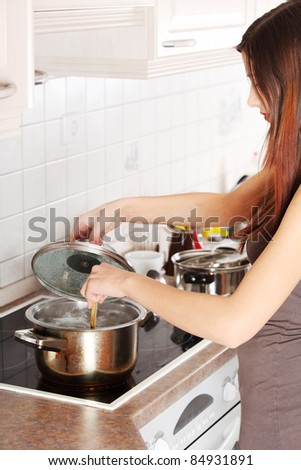 Young woman cooking in her kitchen