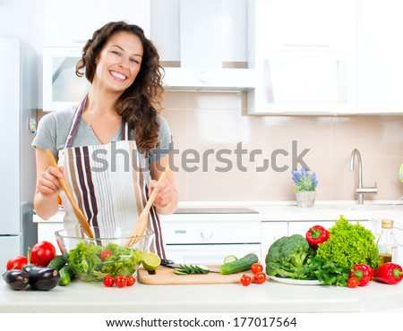 Young Woman Cooking in the kitchen. Healthy Food - Vegetable Salad. Diet. Dieting Concept. Healthy Lifestyle. Cooking At Home. Prepare Food