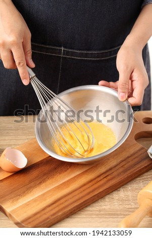 Young woman cooking omlet on wooden table Stok fotoğraf ©