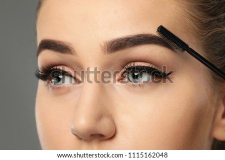 Young woman correcting shape of eyebrows on grey background, closeup