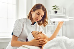 Young woman cosmetologist or dermatologist directing lamp for facial treatment to lying young woman in beauty spa salon. Facial treatment, massage, skincare, cosmetology concept
