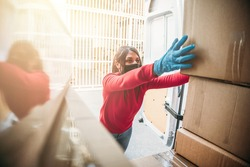 Young woman courier loads package from hes delivery van wearing face mask and gloves during global Coronavirus Covid-19 pandemic - Concept of fast and safe shipping
