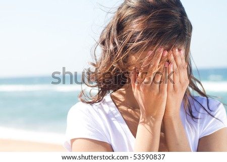 young woman cover her face with hands
