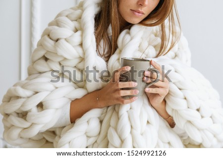 Young woman covered with chunky merino wool blanket on white background. Cozy winter style. Сток-фото ©