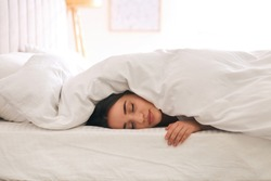 Young woman covered with warm white blanket sleeping in bed at home