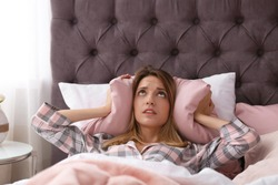 Young woman covering ears with pillow while trying to sleep in bed at home. Early morning