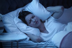 Young woman covering ears with pillow while trying to sleep in bed at night