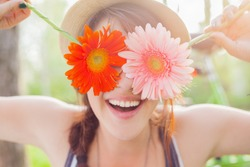 Young woman covering her eyes with fresh colorful flowers. Enjoying spring time