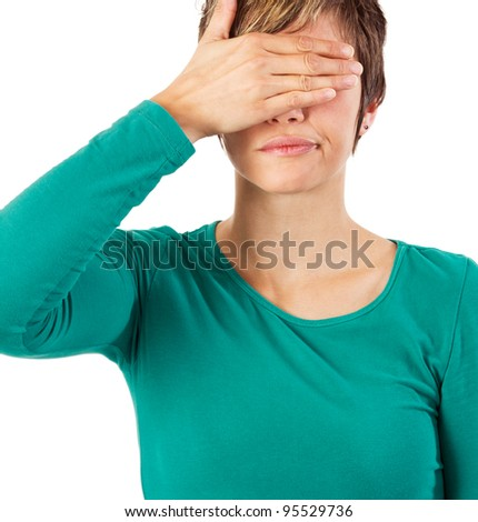 Young woman covering her eyes with her hand. Studio shot against a white background.