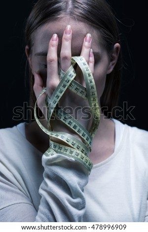 Young woman covering her face by her hand with the centimeted tied around her fingers Stock fotó ©