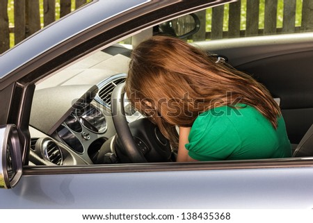 Young woman covering her face with hands sitting depressed in car