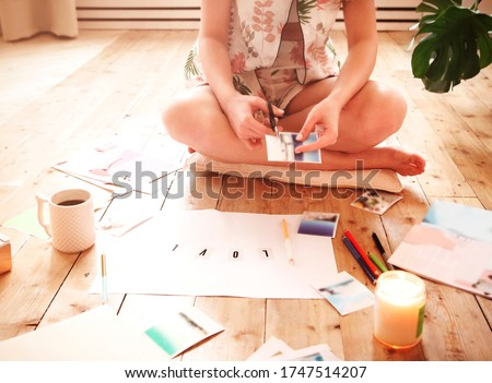 Young woman creating her Feng Shui wish map using scissors. Dreams and wishes
