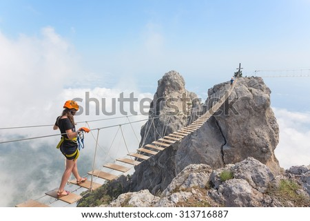 Young woman crossing the chasm on the rope bridge #313716887