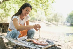 Young woman crouched under a tree cooking sausages in the barbecue, leisure activities on vacation.