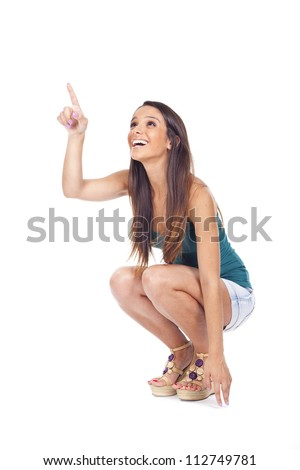 Young woman crouching with his finger pointing to smile...