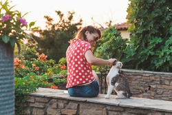 Young woman cuddling a stray cat in the garden