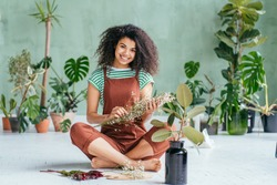 Young woman cultivating home plants.Small business.Sensual mixed race female florist with flowers in hands against background of indoor plants. Life lover, zero waste, inspiration, summer mood concept