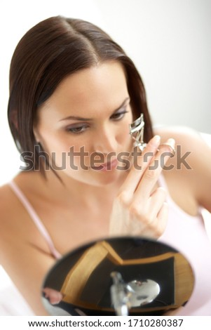 Young woman curling eyelashes before work