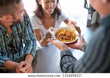 Young woman customer smiling with pleasure while getting pasta at food truck counter
