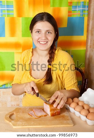 Young woman cutting bacon on cutting board in her kitchen