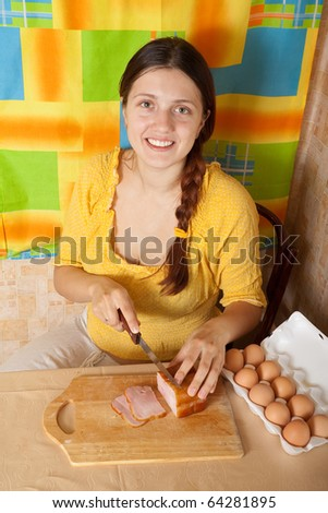 Young woman cutting bacon on cutting board in her kitchen. One of the stages of preparation of bacon and eggs.  See series - stock photo