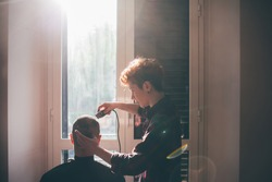 Young woman cutting the hair of a men indoor at home - har care, hair cut, self isolation concept