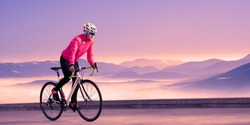 Young Woman Cyclist Riding Road Bike on the Road in the Beautiful Mountains at Purple Sunset. Adventure, Travel, Healthy Lifestyle and Sport Concept.