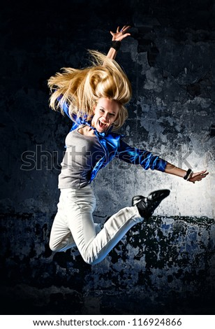 Young woman dancer jumping. At wall background.