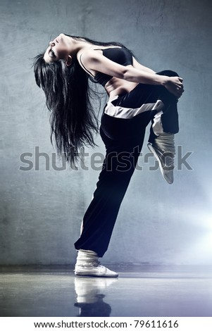 Young woman dancer. On wall background.