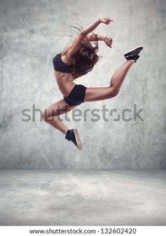 young woman dancer with grunge wall background texture jumping and dancing - stock photo